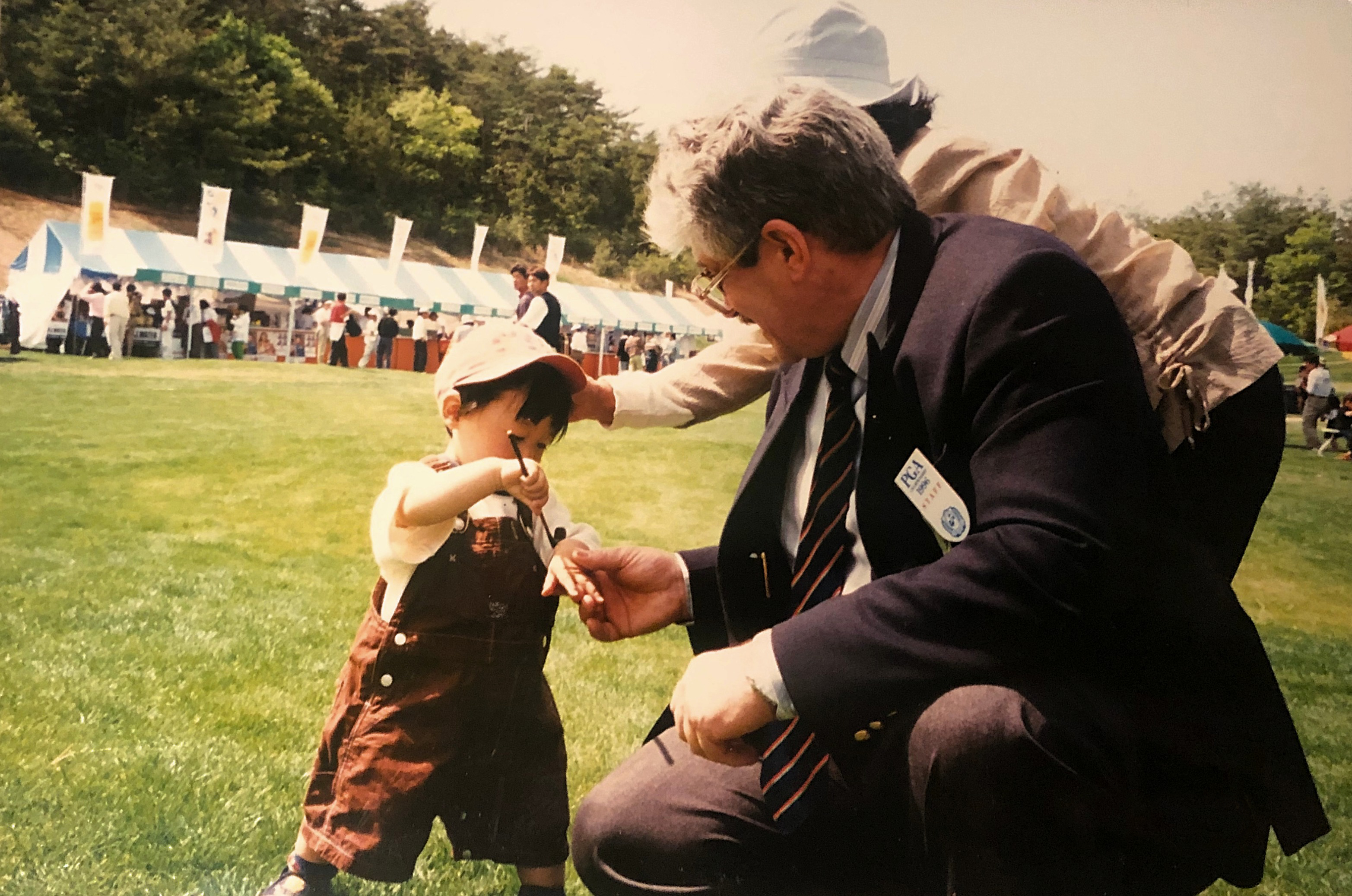 John giving a miniature club to a young Japanese golfer, Japan PGA Championship, 1996